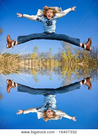 Happy jumping boy. Reflected in the water