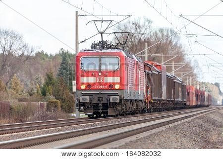 BURG / GERMANY - JANUARY 5 2017: german rail DB (Deutsche Bahn) Class 143 train with goods wagons drives on tracks.