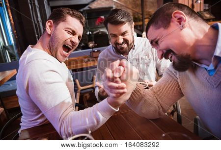 Handsome concentrated brutal man gathering his strength and concentrating on the activity while arm wrestling with his friend.