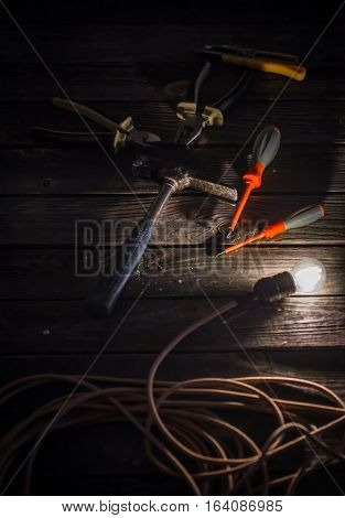 tools for electricians on a wooden background with a burning light bulb
