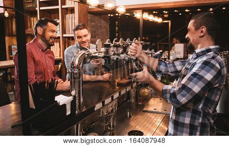 Home made beer. Cheerful bearded positive bar attender standing behind the bar counter and holding a glass while pouring beer into it