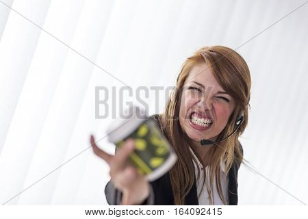 Young business woman yelling on the headphones during a phone call, throwing coffee