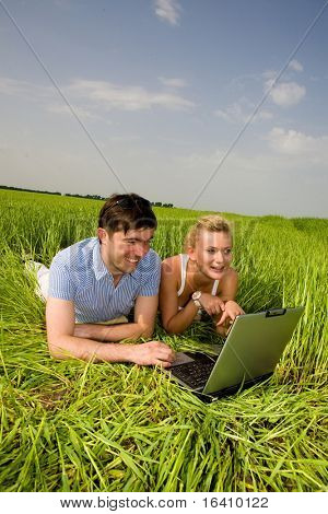 Casual happy couple on a laptop computer outdoors. Lay on the green grass