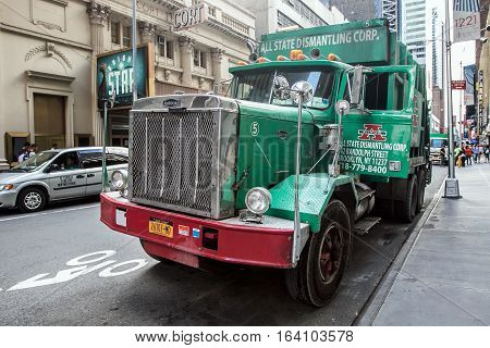 New York August 2 2016: A large green garbage truck parked in the streets of Manhattan.