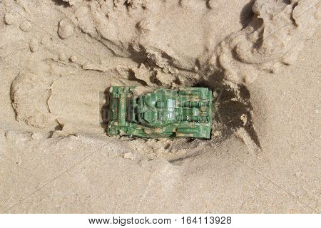 toy tank buried in the sand on the beach