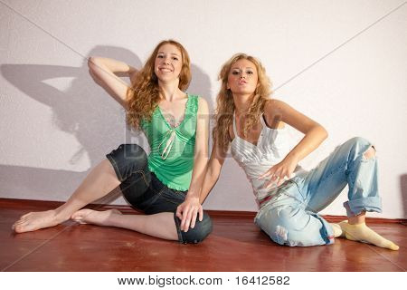 Two attractive young women sitting close on hardwood floor in home smiling and laughing.