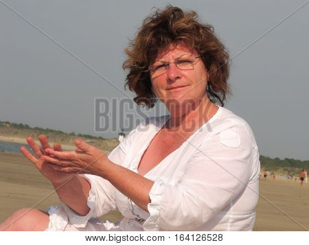 A Beautiful Senior Woman Sitting On The Beach By The Sea