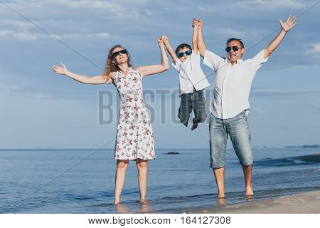 Happy Family Walking On The Beach At The Day Time.