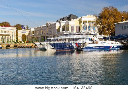 Sochi Russia - November 1 2015: Rescue and border guard motorboat moored at pier in Sochi seaport. In background the shopping gallery Grand Marina. Marine station complex Port. Krasnodarskiy kray Russia