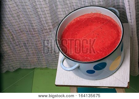 Pan With Tomato Sauce Is On A Stool In The Kitchen. Cooking Homemade Tomato Sauce In The Kitchen.