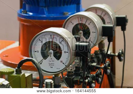 Close up of high-pressure industrial barometers in a hydraulic system.