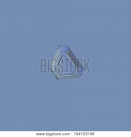 Snowflake isolated on uniform blue background: macro photo of real snow crystal, captured on glass. This is small snowflake of triangular plate type, with simple pattern of straight lines and ridges.