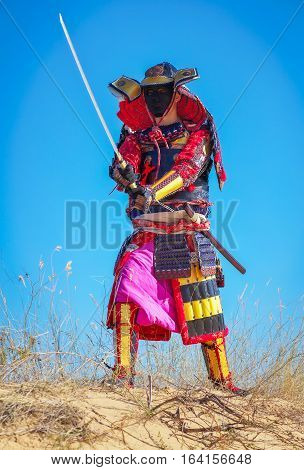 Samurai with sword on the sand. Men in samurai armour on the sand. Original Character