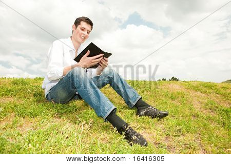 happy man reading a book sitting on the green grass