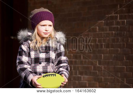 adorable school age girl wearing winter coat holding football