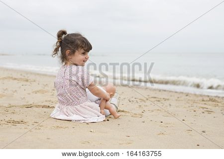 Little Girl With Her Dolly On The Beach