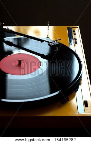 Record player  in yellow case with black tonearm with rotation vinyl record with red label isolated on dark background. Vertical photo side view closeup