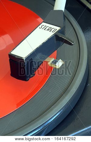 Old vintage record player playing red flexible disc. Vertical top view closeup