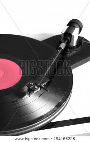 Vintage turntable in silver case playing vinyl record with red label . Vertical photo isolated on white background closeup