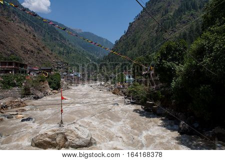 Sacred prayer flags and a bridge across the river Parvati in the Himalayas. Gurdwara Sri Guru Nanak Dev Ji. Manikaran, North India