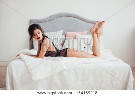 Beautiful sexy woman wearing seductive black lingerie posing in bedroom. Professional make-up and hairstyle. Perfect body and skin. Fashion photo.