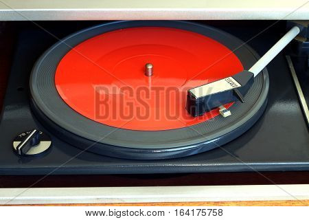 Old vintage record player playing red flexible disc. Horizontal front view closeup