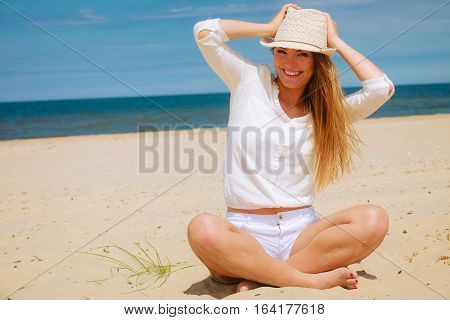 Tourism and traveling. Happy attractive woman tourist resting on sunny beach. Young girl enjoy her free time on seaside. Summer time.