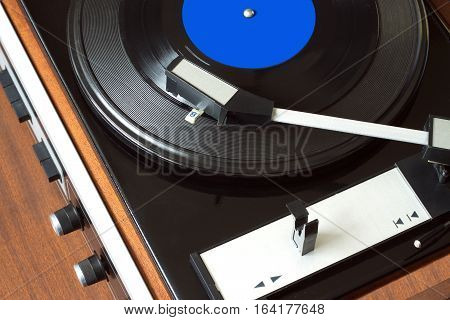 Old vintage vinyl record player in brown wooden case playing LP record with blue label. Top view horizontal photo closeup