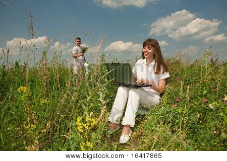 Happy Young Woman on the grass field with a laptop against the background of her beloved husband with a bouquet of flowers in their hands