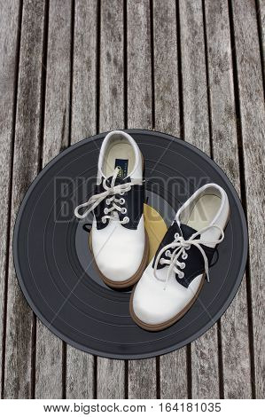 old vinyl record with black and white saddle shoes on top