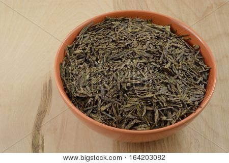Bowl of dry loose lung ching Chinese green tea leaves