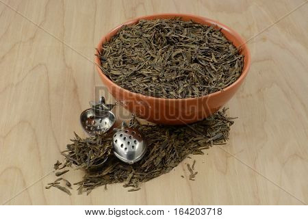 Bowl of dry loose lung ching Chinese green tea leaves and two tea ball infusers