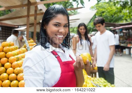 Beautiful laughing mexican saleswoman with customers in the background on a farmers market in latin america