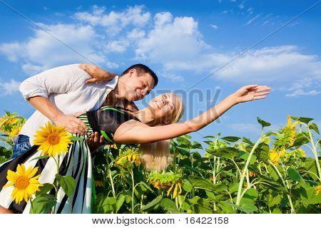 pareja amorosa en un campo de girasoles