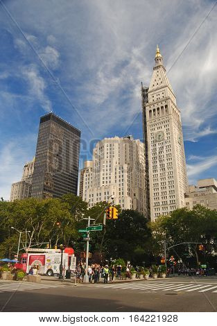New York, United States - September 15, 2014. Street view on intersection of Broadway and 5th avenue in New York, with modern buildings, vegetation and people.