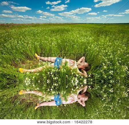 pretty girl having fun in the field. Specular reflection in water