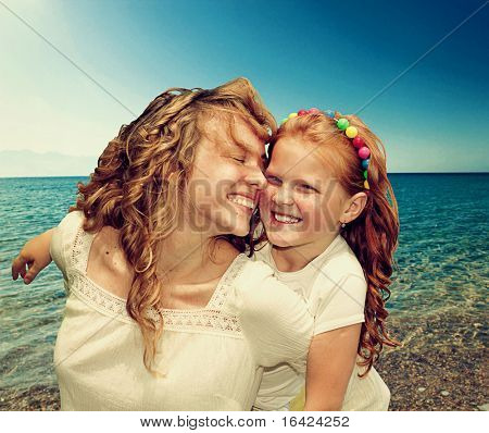 Mom and Daughter Having Fun against azure sea