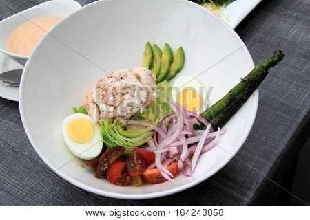 Large white bowl filled with delicious salad of crabmeat,avocado, greens,hard boiled eggs and tomatoes