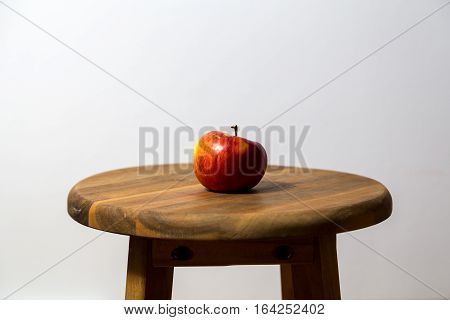 Photography of a single red apple on a wooden stool.