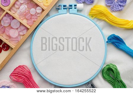Embroidery hoop with blank fabric colored sewing threads and various sewing buttons