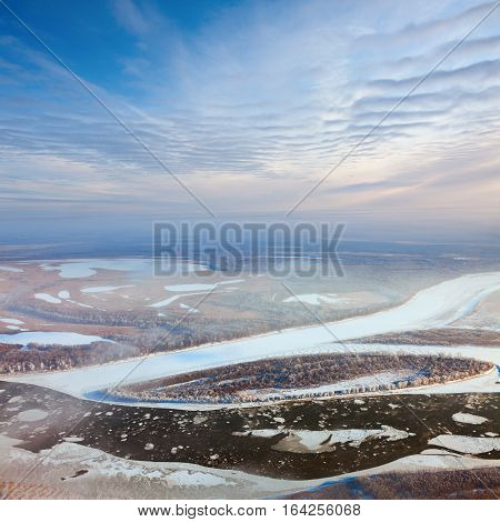 Aerial view of the great river with floating ice floes during sundown. Driving of ice. Ice floe.
