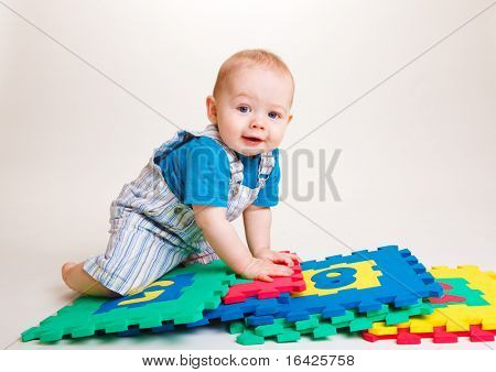 Sweet curious infant boy crawling over puzzles