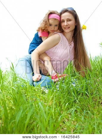 Cheerful mother and her sweet daughter on green grass