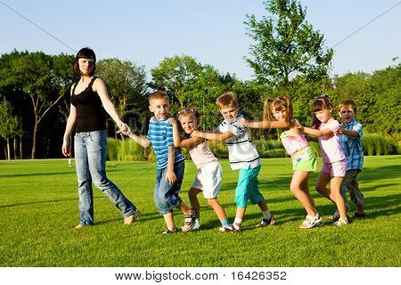 Teacher with kids walking to the city park