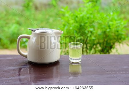 Hot green tea pot and glass on wood table