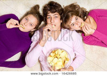 Three teenage friends eating unhealthy crisps