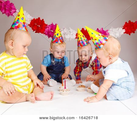 Group of babies looking at cupcakes with birthday candles