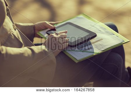 Business woman sitting on a bench in a park, working on a lunch break