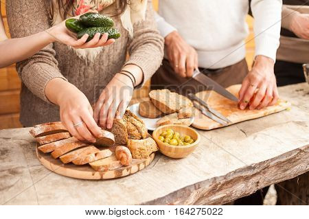 the yong people cuts bread and tomatoes on a wooden board. To cook food in kitchen, outdoors.