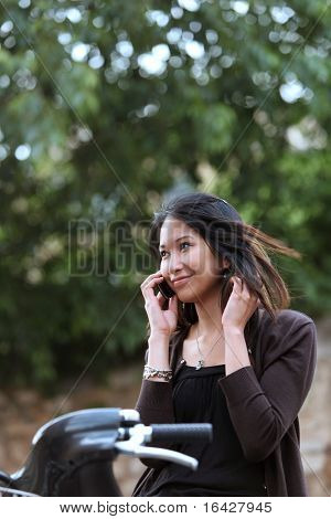 Young woman on a bicykle calling on her cell phone